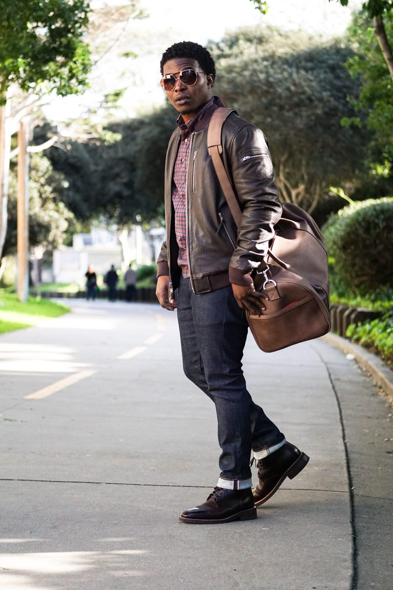 dapper-advisor-black-man-wearing-brown-leather-bomber-jacket-holding-brown-leather duffle bag-3