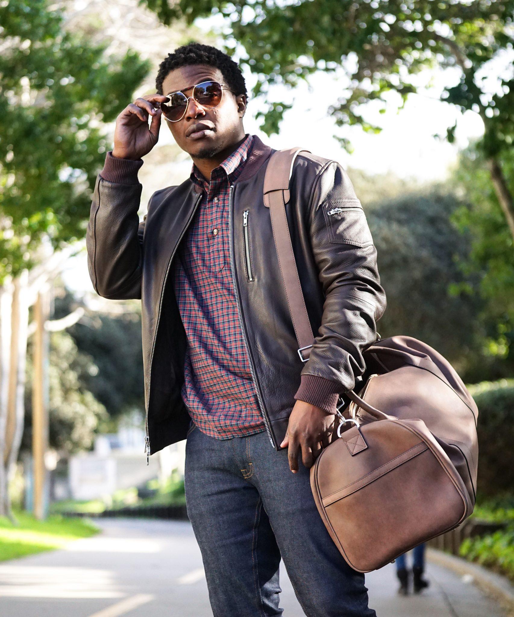 dapper-advisor-black-man-wearing-brown-leather-bomber-jacket-holding-brown-leather duffle bag-1