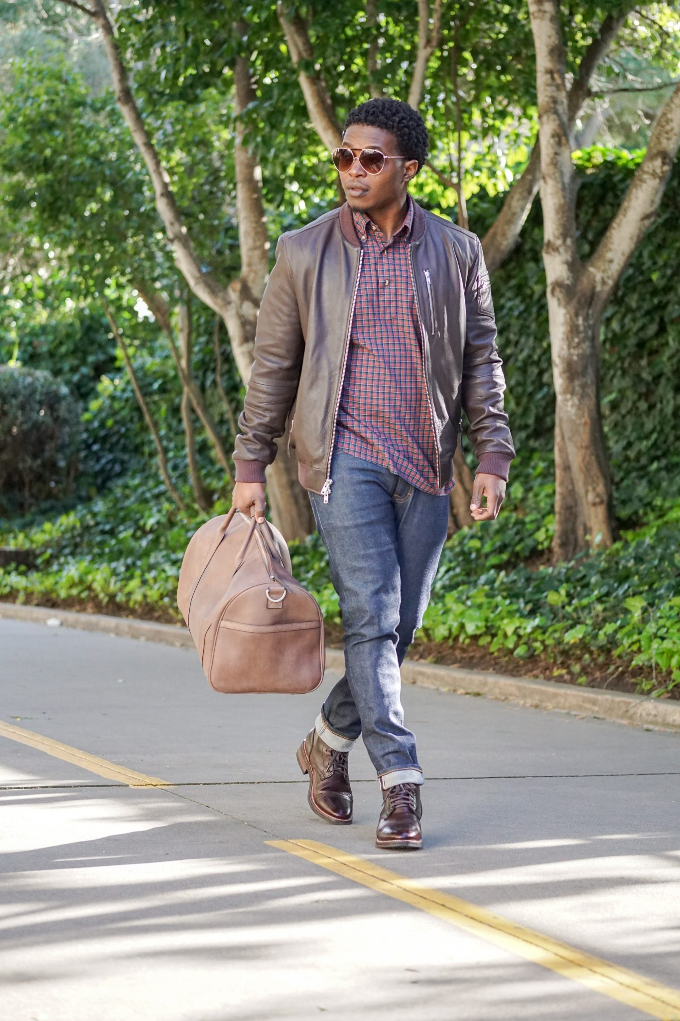 dapper-advisor-black-man-wearing-brown-leather-bomber-jacket-holding-leather duffle bag-brown-leather-thursday-boots-1