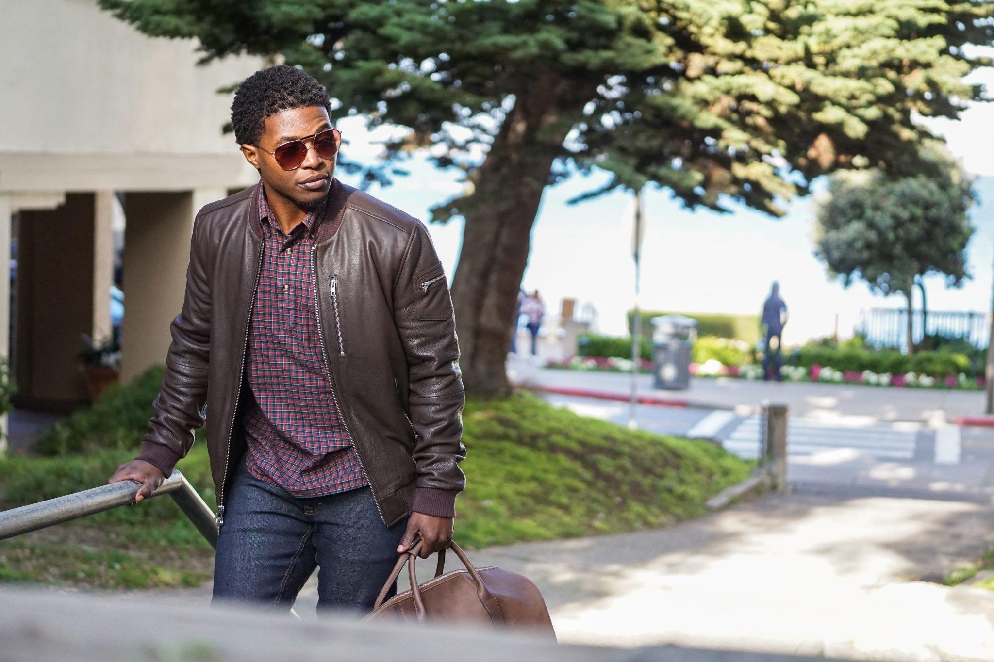 dapper-advisor-black-man-wearing-brown-leather-bomber-jacket-holding-leather duffle bag-2