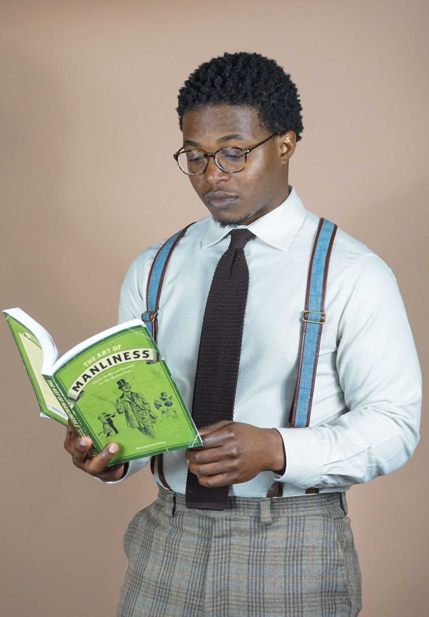 dapper-advisor-black-man-reading-books-wearing-shirt-tie-suspenders-plaid-pants-spring