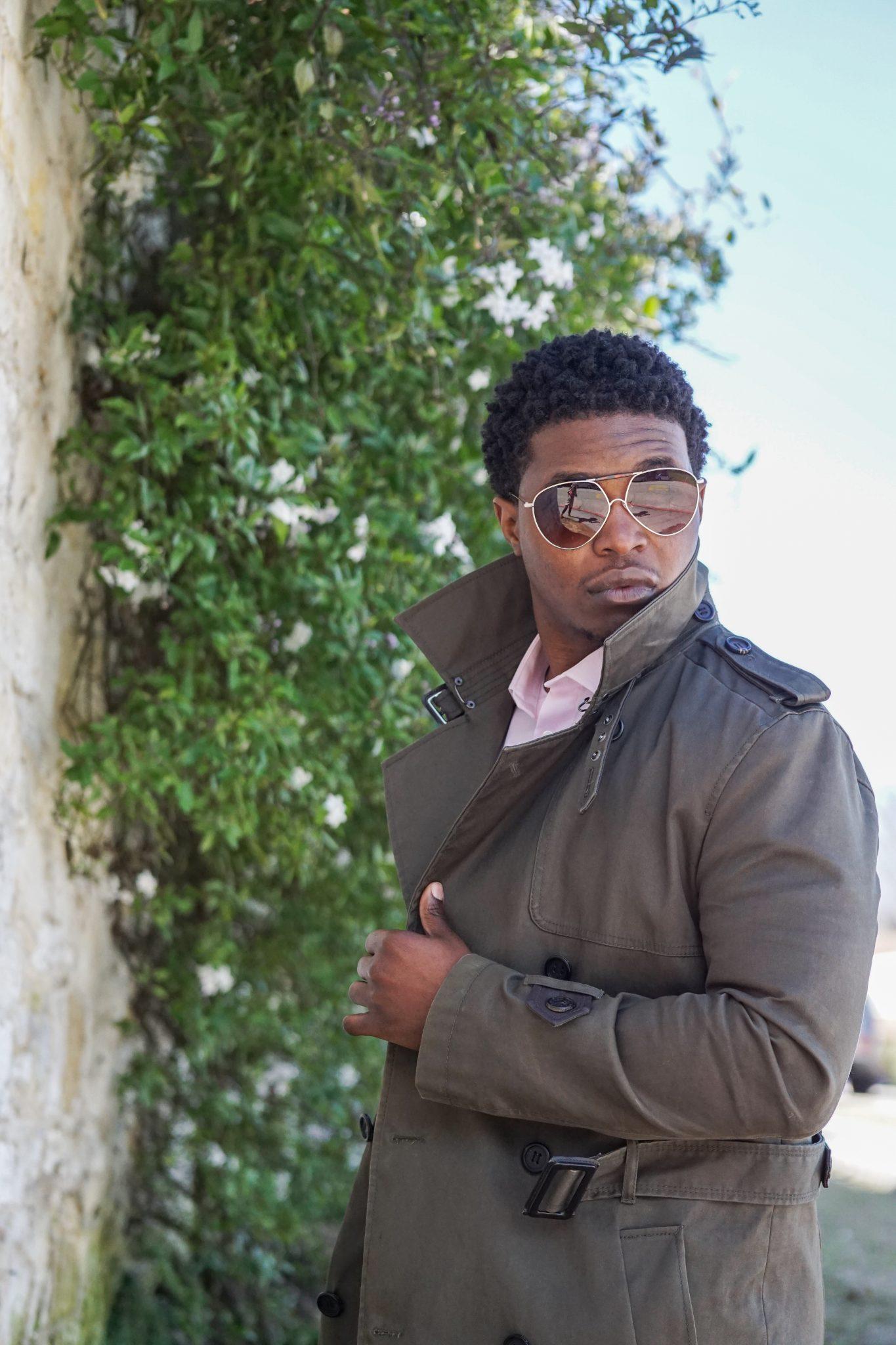 dapper-advisor-black-man-wearing-olive-trench coat-pink-shirt-aviator-glasses