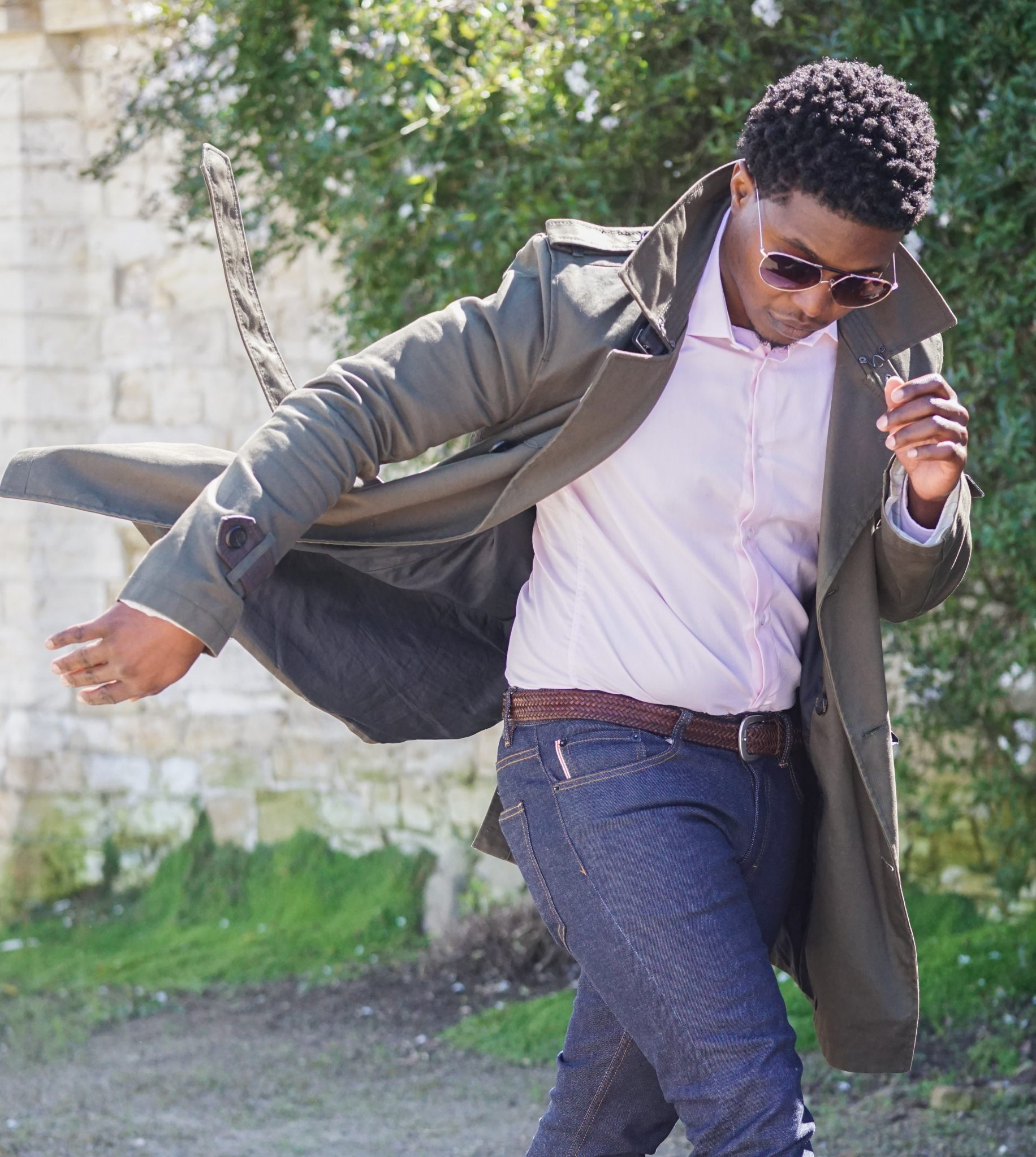 dapper-advisor-black-man-wearing-trench coat-pink-shirt-brown-woven-belt-windy