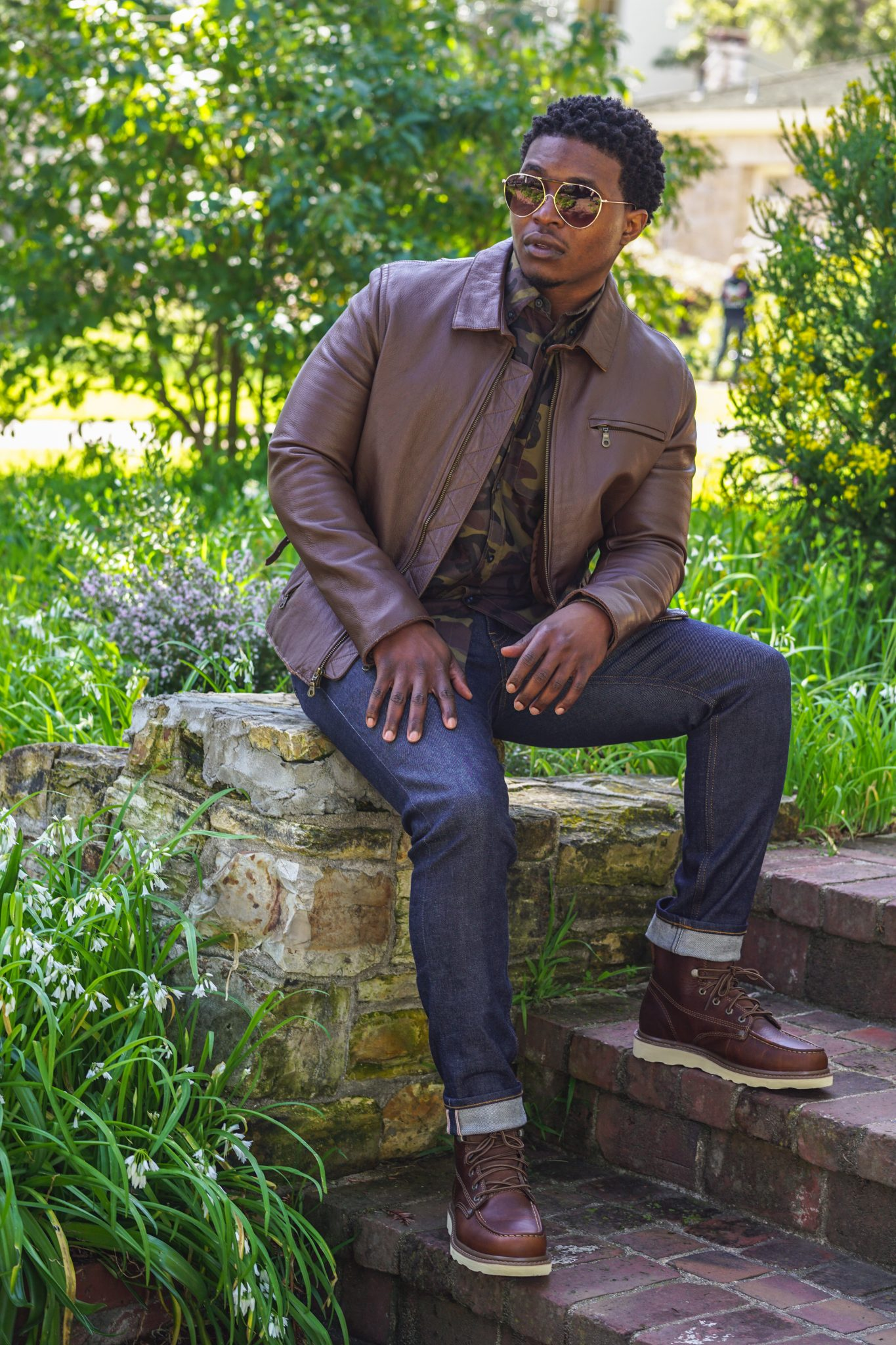 dapper-advisor-black-man-wearing-earth tones-brown-leather-jacket-camo-shirt-raw-denim-jeans-moc-toe-boots-1