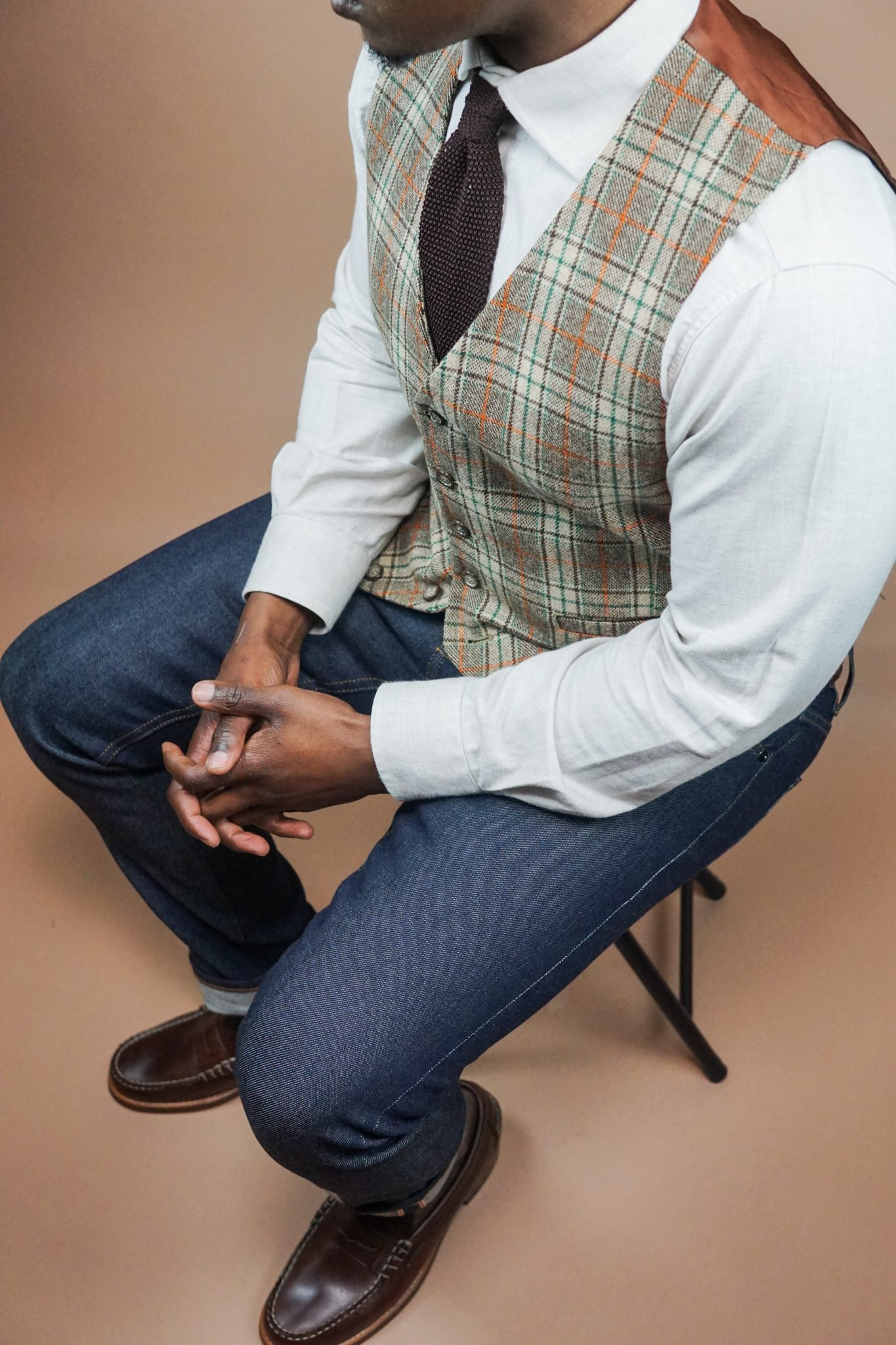 dapper-advisor-casually tailored-plaid-waistcoat-raw-denim-jeans-silk-knit-tie-leather-penny-loafers-1