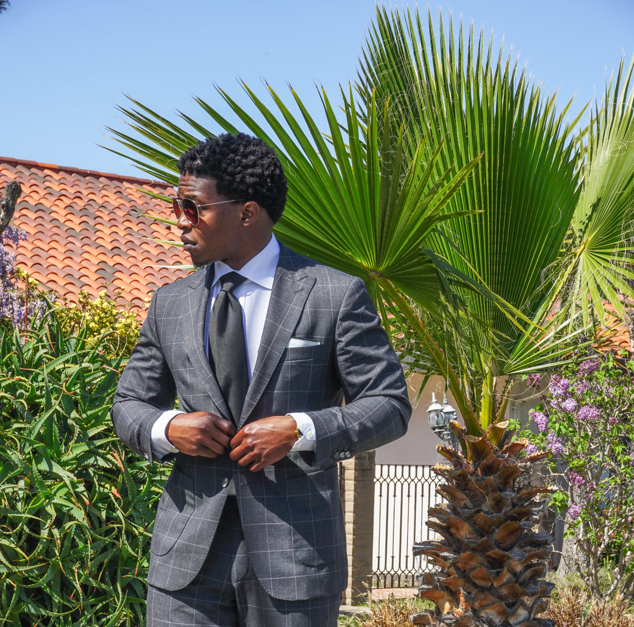dapper-advisor-black man wearing-grey windowpane suit-white shirt-black tie-1