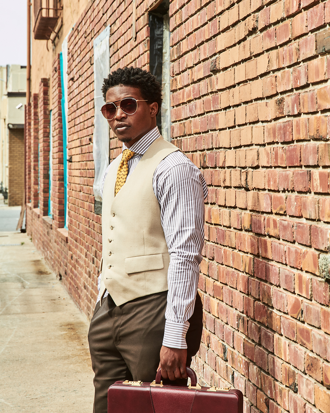 dapper advisor-black man-wearing-linen waistcoat-yellow-hermes-tie-brown-stripe-suitsupply-shirt-hard case-briefcase
